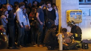 A member of the French fire brigade aids an injured individual near the Bataclan concert hall following fatal shootings in Paris